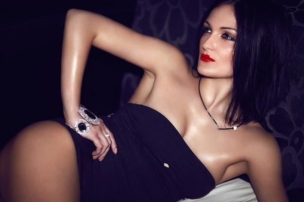 Haute couture look.glamor portrait de beau sexy caucasien jeune femme brune modèle avec maquillage lumineux avec des lèvres rouges avec un corps parfait en lingerie noire