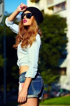 Haute couture look.glamor style de vie blonde femme fille modèle en jeans décontractés shorts en tissu à l'extérieur dans la rue en casquette noire à lunettes