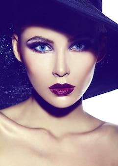 Haute couture look.glamour closeup portrait de beau sexy élégant jeune femme modèle avec maquillage lumineux avec des lèvres rouges avec une peau parfaitement propre en tissu décontracté en chapeau