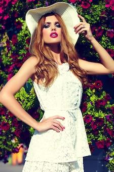 Haute couture look.glamour closeup portrait de belle sexy blonde élégante jeune mannequin avec maquillage lumineux et lèvres roses avec une peau parfaitement propre en chapeau près de fleurs d'été