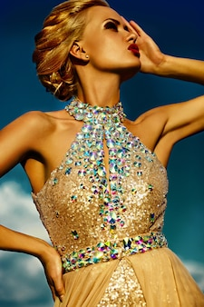 Haute couture look.glamour closeup portrait de belle sexy blonde élégante jeune mannequin avec un maquillage lumineux et des lèvres rouges avec une peau propre au soleil parfaite avec des bijoux à l'extérieur dans un style vogue en e