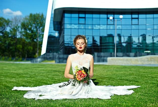 Haute couture look.glamour closeup portrait de belle sexy blonde élégante mariée jeune femme modèle avec maquillage lumineux, avec des lèvres rouges assis sur l'herbe en robe de mariée avec des fleurs