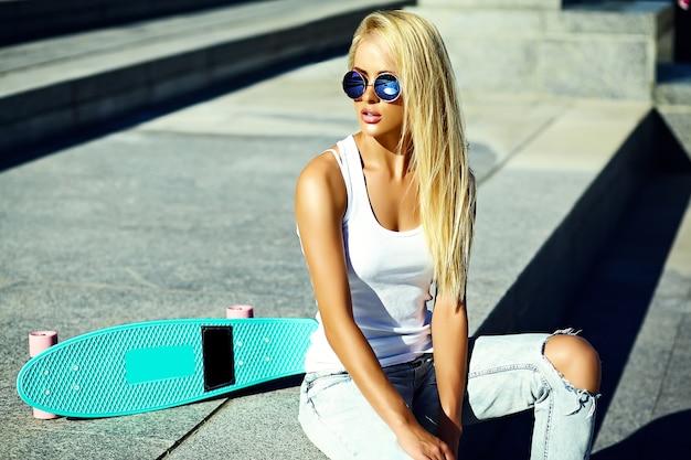 Haute couture look.glamour élégant sexy belle jeune blonde mannequin fille en été brillant vêtements décontractés hipster avec planche à roulettes assis dans la rue