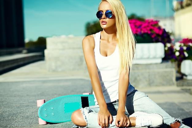 Haute couture look.glamour élégant sexy belle jeune blonde modèle fille en été vêtements hipster décontractés lumineux avec planche à roulettes derrière le ciel bleu dans la rue