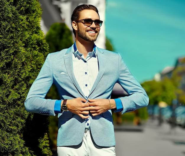 Haute couture look.young élégant confiant heureux beau modèle d'homme d'affaires en costume vêtements style de vie dans la rue en lunettes de soleil