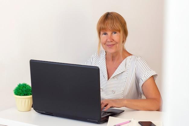 Haute femme à l'aide d'un ordinateur portable. femme affaires, travailler, a, ordinateur portable, bureau