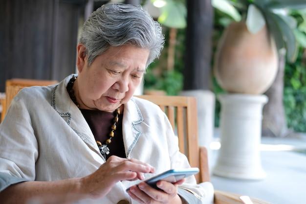 Haute femme à l'aide de téléphone intelligent mobile. femme âgée, tenue, téléphone portable