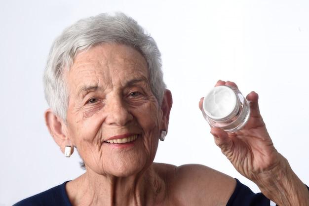 Haute femme appliquant une crème pour la peau ou un hydratant sur son visage