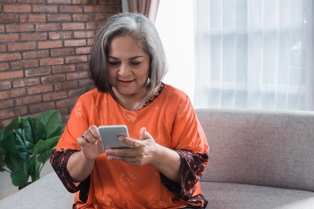Haute femme asiatique à l'aide de son téléphone intelligent