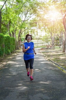 Haute femme asiatique heureuse jogging en cours d'exécution dans le parc