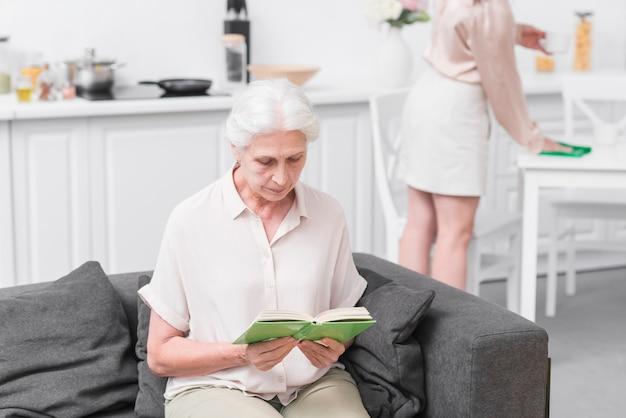 Haute femme assise sur le canapé, lecture de livre à la maison