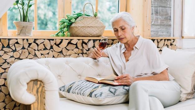 Haute femme assise sur un canapé tenant un livre de lecture de verre à vin