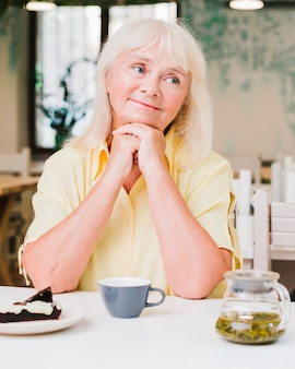 Haute femme assise dans la cuisine avec une tasse et un gâteau