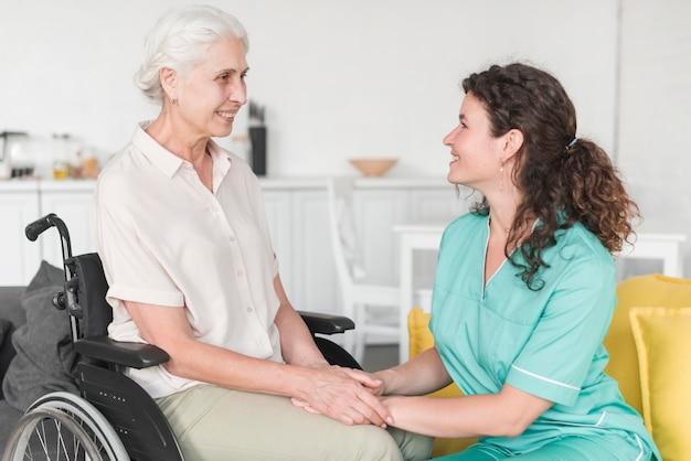 Haute femme assise sur un fauteuil roulant tenant la main de l'infirmière