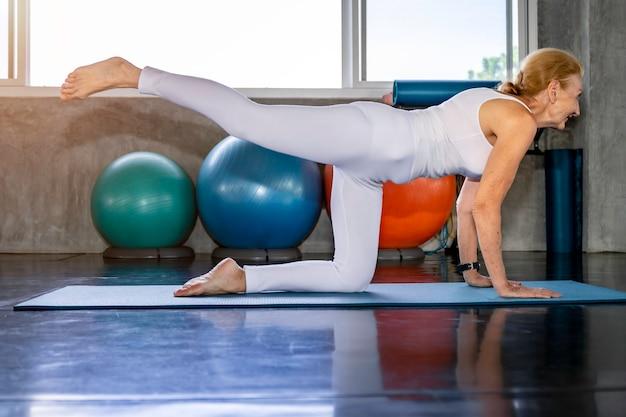 Haute femme caucasienne, faire des exercices de yoga au gymnase de remise en forme.