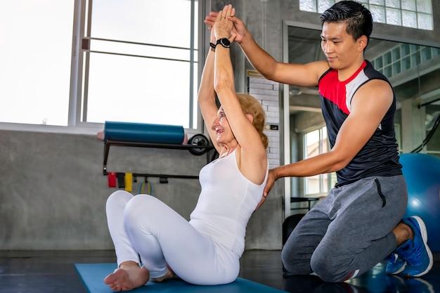 Haute femme caucasienne en formation de vêtements de sport yoga avec entraîneur masculin au fitness.