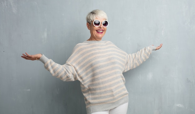 Haute femme cool contre le mur de ciment grunge.