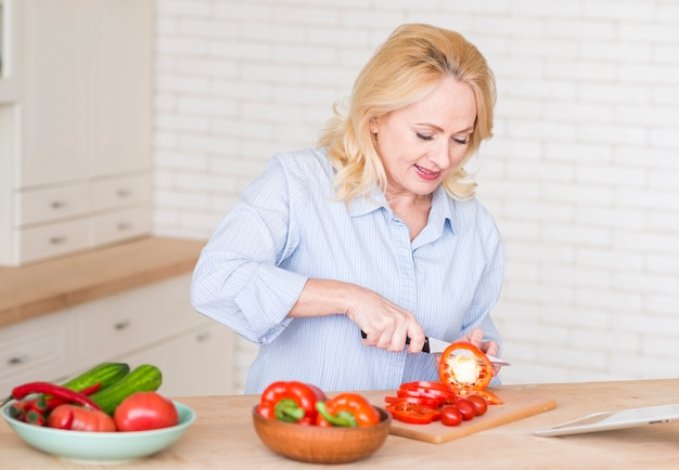 Haute femme couper les tranches de poivron rouge avec un couteau sur une planche à découper dans la cuisine