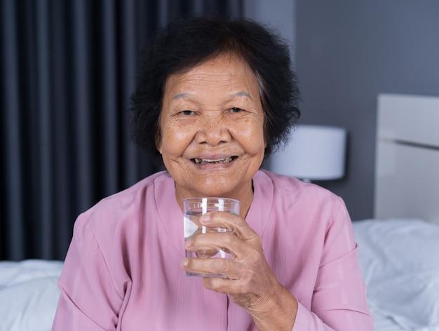Haute femme l'eau potable dans la chambre