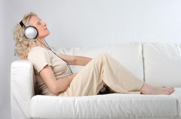 Haute femme écoutant de la musique sur des écouteurs