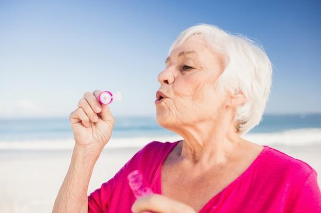 Haute femme faisant des bulles avec une baguette à bulles