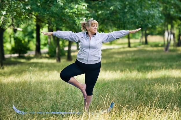 Haute femme faisant du yoga dans le parc sur un tapis