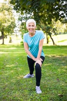 Haute femme faisant des exercices d'étirement dans le parc