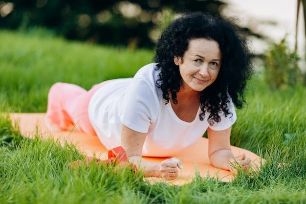 Haute femme faisant la planche de yoga asana en plein air et à la recherche. vue de face