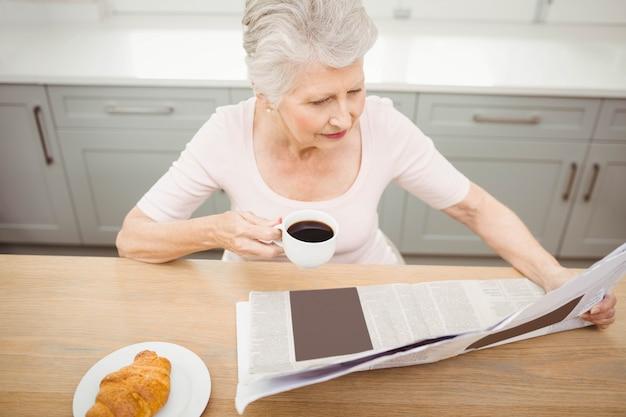 Haute femme lisant un journal à la maison