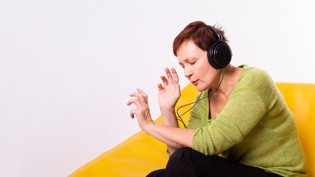 Haute femme relaxante en écoutant de la musique