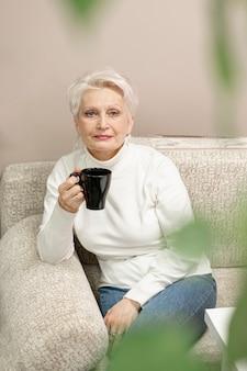 Haute femme senior appréciant une tasse de café