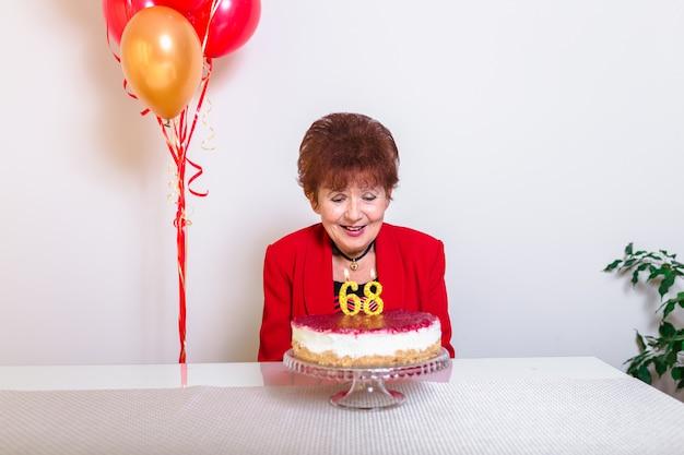 Haute femme soufflant des bougies sur un gâteau