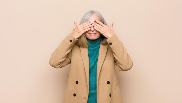 Haute femme souriante et heureuse, couvrant les yeux des deux mains et attendant une surprise incroyable