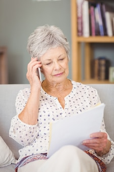 Haute femme tenant un téléphone portable tout en regardant les documents