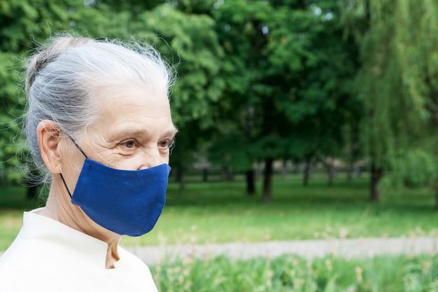 Haute femme en tissu masque de protection à l'extérieur. concept de protection antivirus pour les seniors