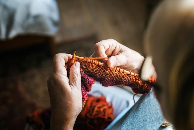 Haute femme tricotant à la maison