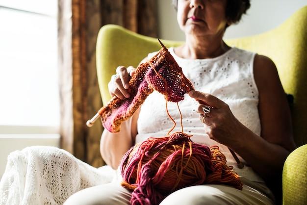 Haute femme à tricoter pour passe-temps à la maison