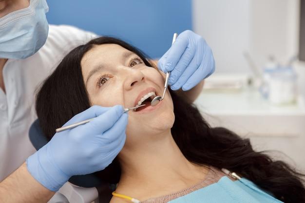 Haute femme visitant un dentiste à la clinique dentaire