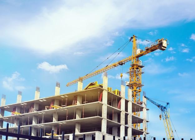 Haute grue jaune construisant une maison dans le beau ciel bleu clair avec des nuages. les travailleurs du bâtiment en construction construisent une maison.