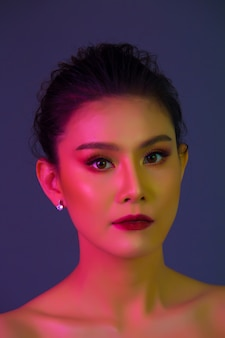 Haute modèle femme dans des lumières colorées posant