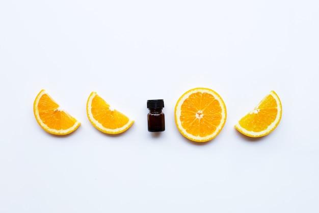 Haute teneur en vitamine c, fruits orange avec une bouteille d'huile essentielle sur blanc