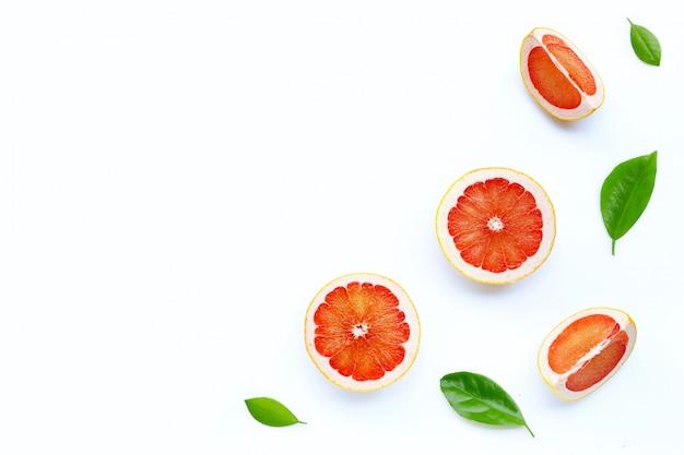 Haute teneur en vitamine c. tranches de pamplemousse juteuses avec des feuilles vertes sur fond blanc.
