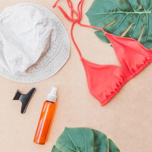 Haute vue angle, de, bikini, parfum, hairclip, et, feuille, sur, arrière-plan beige