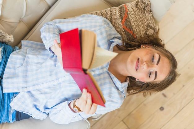 Haute vue angle, de, femme, lecture, livre, quoique, couché, sur, sofa
