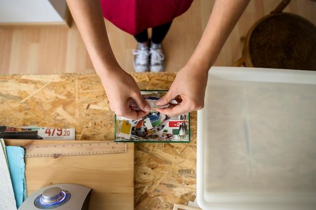Haute vue angle, de, main femme, déchirer, papier, dans, morceaux, dans, atelier
