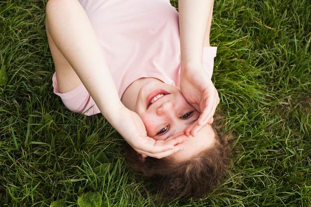 Haute vue angle, de, sourire, fille, coucher herbe, et, protéger, yeux