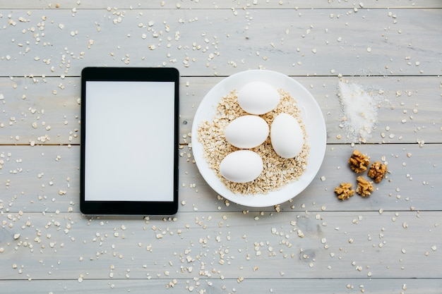 Haute vue angle, de, tablette numérique, près, oeufs, à, avoine, sur, plaque