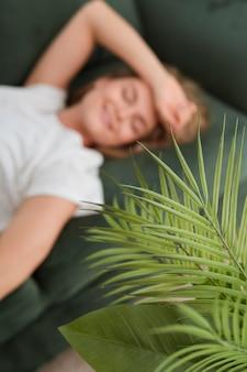 Haute vue floue femme assise sur un canapé