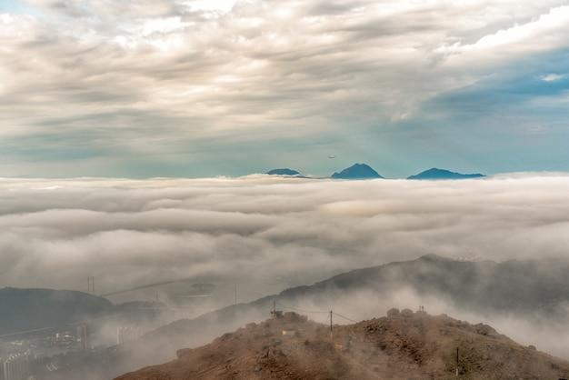 De hautes montagnes couvertes de brouillard pendant la journée