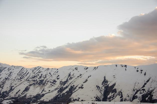 De hautes montagnes avec des pics enneigés contre un beau ciel d'avant l'aube avec des nuages